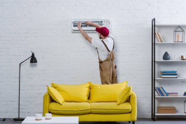 professional repairman changing filter for air conditioner hanging on white brick wall