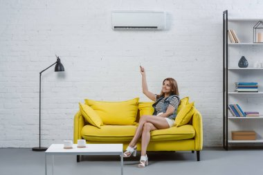 beautiful young woman sitting on sofa and pointing at air conditioner with remote control