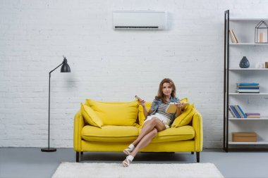 focused young woman with book sitting on sofa and pointing at air conditioner with remote control