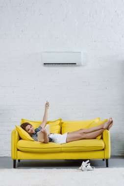 happy young woman reading book on sofa and pointing at air conditioner with remote control