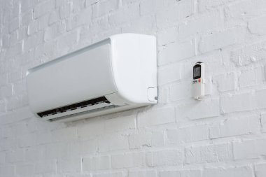air conditioner hanging on white brick wall with remote control