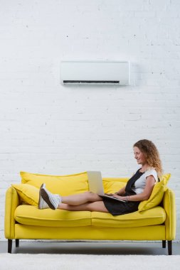 Happy young woman working with laptop while sitting on couch under air conditioner hanging on wall stock vector