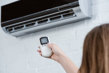 Cropped shot of woman pointing at air conditioner with remote control stock vector