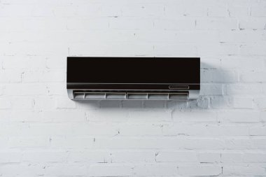 Modern air conditioner hanging on white brick wall stock vector