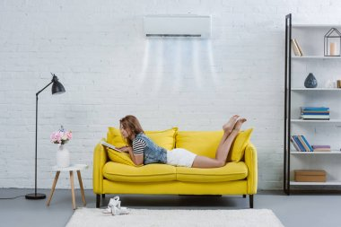 attractive young woman reading book on couch under air conditioner hanging on wall