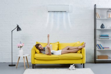 happy young woman reading book on couch and pointing at air conditioner hanging on wall with remote control