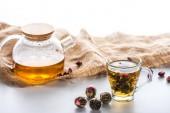 pohár z čínských kvetoucí čaj, konvice, hadřík a čajové kuličky na stole