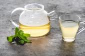 glass cup and teapot of healthy tea with mint on grey surface