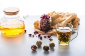 dried rose buds in jar, cup of chinese flowering tea with tea balls on white tabletop