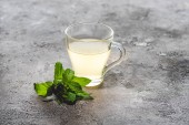 cup of healthy tea with mint on grey surface