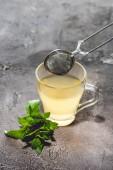 Fotografie zdravý čaj s mátou a čajové sítko na šedém povrchu