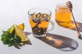 healthy black tea with honey, lemon and mint on white tabletop