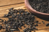 aromatic dried black tea on wooden table in kitchen