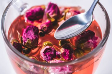 close up of tea with dried pink rose buds and spoon