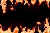 Fotografie pohled na hořící oranžový plamen s prázdné místo ve středu na černém pozadí na plochu