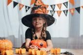 portrét rozkošný dítě v čarodějnice halloween kostým na desku stolu s dýně doma