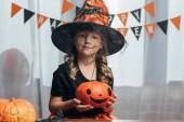 Fotografie portrét roztomilé dítě v čarodějnice halloween kostým hospodářství dýně doma