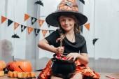 Fotografie portrét usměvavého dítěte v čarodějnice halloween kostým s černý hrnec plný cukroví doma