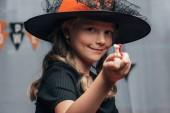 Ať se usmívám dítě v čarodějnice halloween kostým zobrazeno bonbony v ruce doma