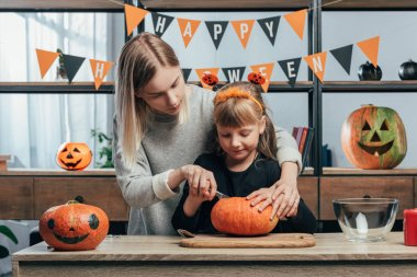 Young woman helping little sister in halloween costume carving pumpkins at home stock vector