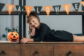 Photo portrait of smiling kid looking at camera in decorated room for halloween