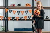 Fotografie adorable kid with pumpkin standing on ladder at hanging flags with happy halloween inscription at home