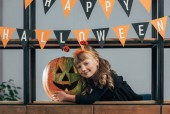Fotografie portrait of smiling child in halloween costume at carved pumpkin and hanging flags at home
