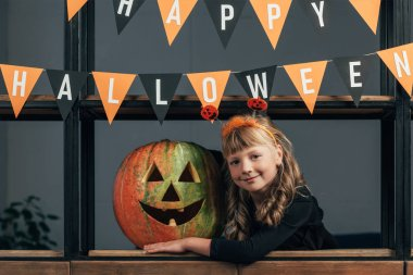 portrait of smiling child in halloween costume at carved pumpkin and hanging flags at home
