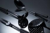 Fotografia vista ravvicinata di utensili in acciaio inox lucido riflette su grey