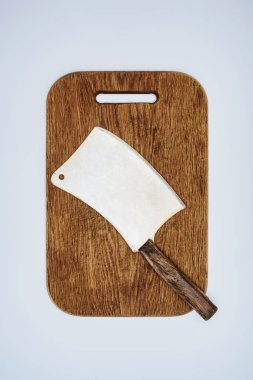 Top view of meat cleaver on wooden cutting board isolated on grey stock vector