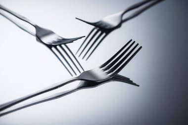 close-up view of three shiny forks reflected on grey