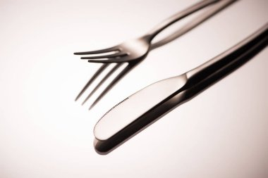 close-up view of shiny fork and knife reflected on grey