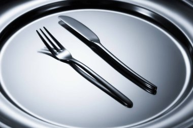 close-up view of fork and knife arranged on shiny metal tray