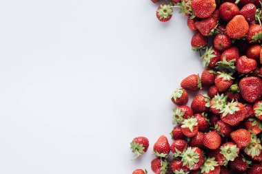 top view of pile of strawberries on white surface with blank copy space