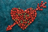 Fotografie top view of heart pierced with arrow sign made of strawberries on blue concrete surface