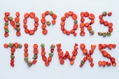 Fotografie top view of part of alphabet letters made of ripe sliced strawberries on white surface
