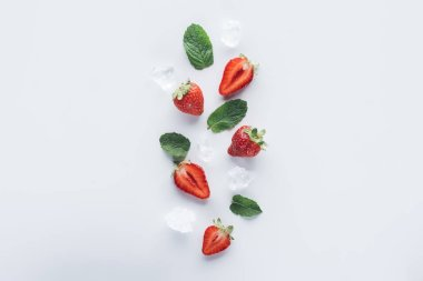 top view of ripe halved strawberries with mint leaves and ice cubes on white surface