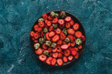 top view of bowl with ripe sliced strawberries on blue concrete surface