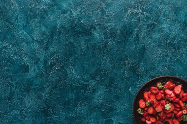 top view of bowl with ripe strawberries on blue concrete surface