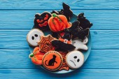 elevated view of plate with spooky homemade halloween cookies on wooden table