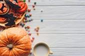 pohled z dýně, deska s halloween cookies, cukroví a šálku s mlékem na dřevěné pozadí