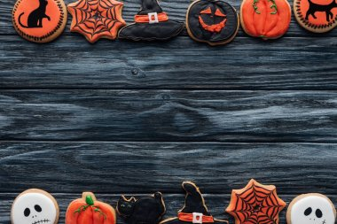 top view of arranged halloween homemade cookies placed in rows on wooden background