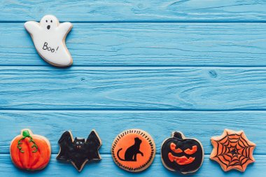 elevated view of spooky halloween cookies on blue wooden background