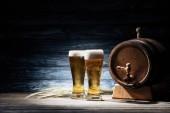 čerstvé pivo v brýle, klásky pšenice a sud piva na dřevěný stůl, oktoberfest koncepce