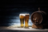 Fotografie two glasses of beer, wheat spikelets and beer barrel on wooden table, oktoberfest concept