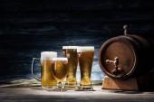 Fotografie brýle chutné pivo, klásky pšenice a sud piva na dřevěný stůl, oktoberfest koncepce