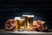 still life of glasses of beer and tasty pretzels on wooden table, oktoberfest concept