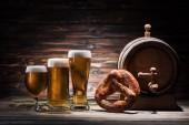 Fotografie glasses of beer, tasty pretzel and beer barrel on wooden table, oktoberfest concept