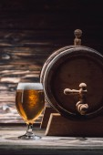 Fotografie glass of fresh beer and beer barrel on wooden table, oktoberfest concept