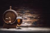 Fotografie sklenice piva a pivní sud na dřevěný stůl, oktoberfest koncepce